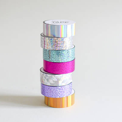 Stack of seven rolls of coloured holographic tape